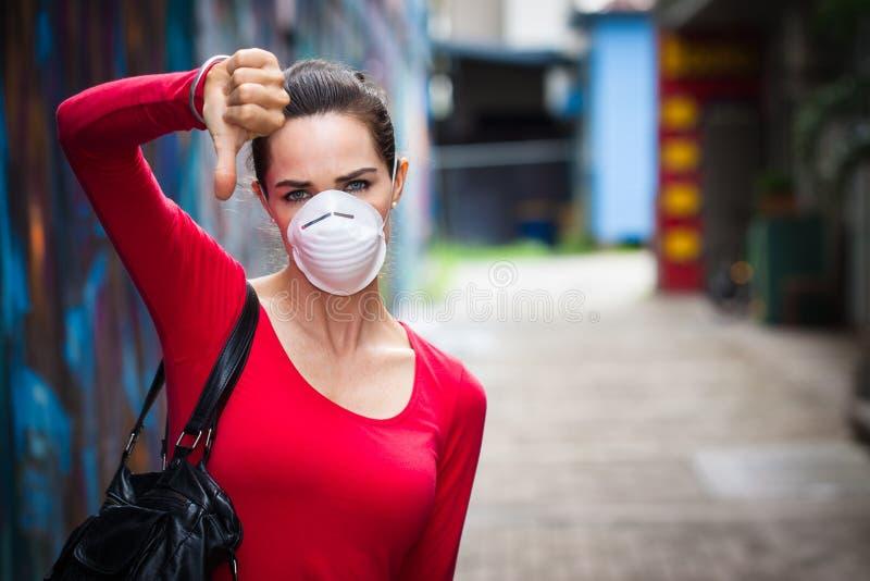 Tragende Maske der Frau, die unten Daumen tut lizenzfreie stockfotografie