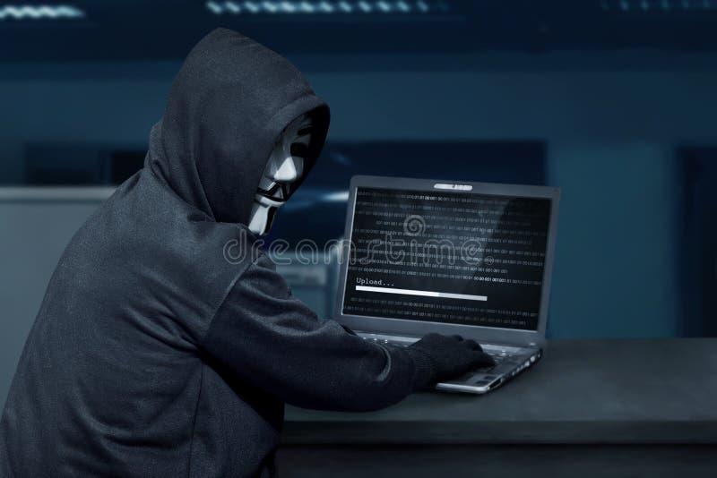 Tragende Maske des Hackermannes unter Verwendung des Laptops, zum des Computervirus zu laden lizenzfreie stockbilder