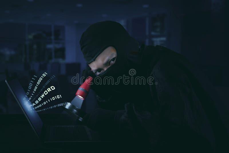 Tragende Maske des Hackers unter Verwendung des Blitzlichts stockbild