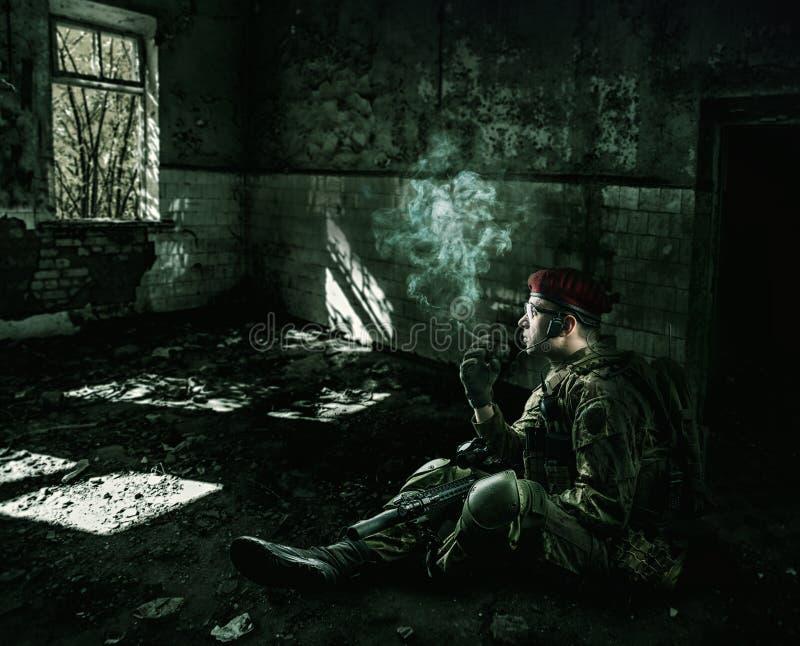 Tragende Militäruniform des Soldaten im zerstörten Gebäude stockfotografie