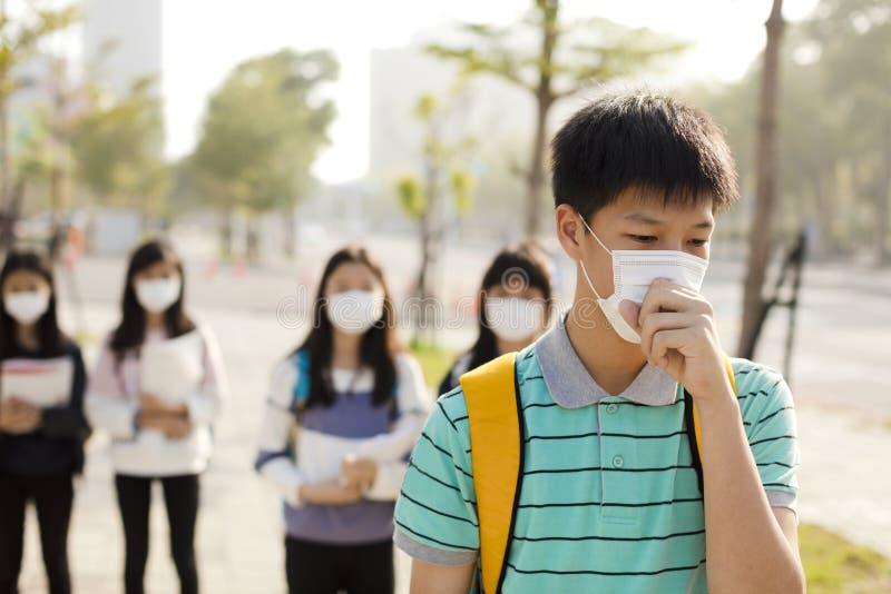 Tragende Mundmaske des Studenten gegen Smog in der Stadt stockbild