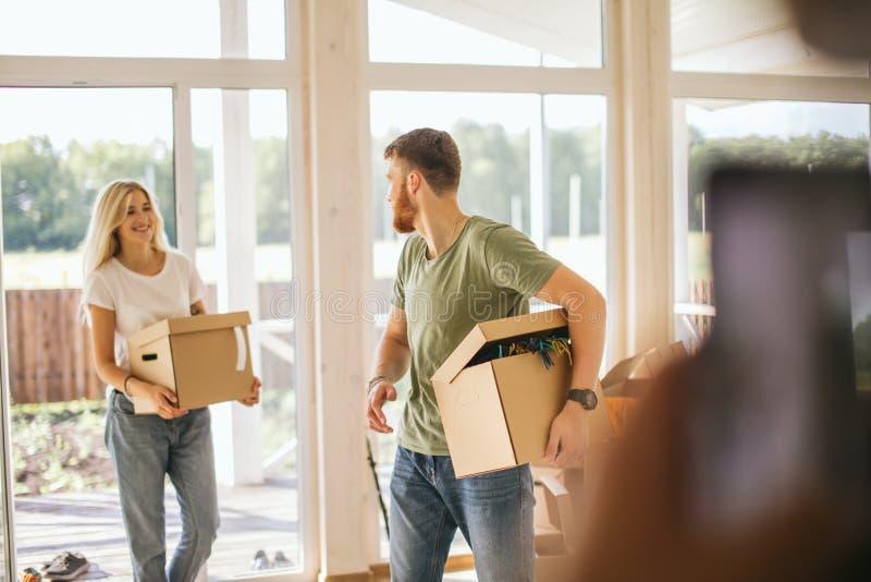 Tragende Pappschachteln des glücklichen Paars in neues Haus an beweglichem Tag lizenzfreies stockfoto