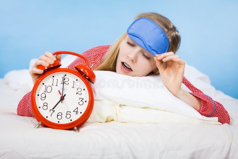 Tragende Pyjamas der Schlafenfrau, die Uhr halten lizenzfreie stockbilder