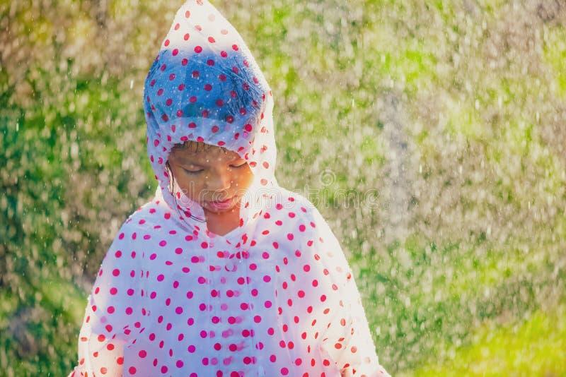 Tragende Regenmantelstellung des traurigen asiatischen Kindermädchens unter dem Regen stockfotos