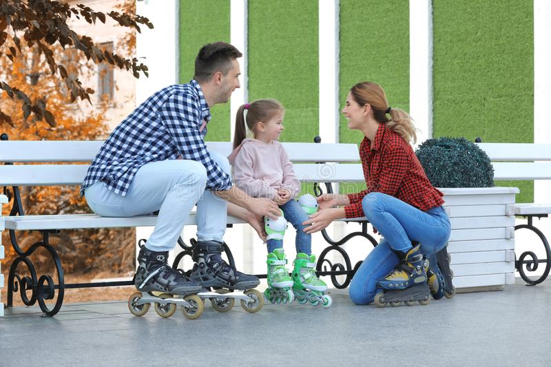 Tragende Rollschuhe der glücklichen Familie stockbild