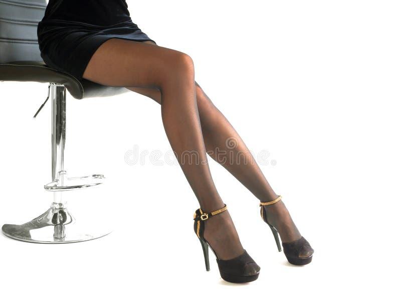 Tragende Schuhe der hohen Absätze der sexy Frau und kurzer Rock, die im Bürostuhl sitzen Lokalisiert auf Weiß stockbilder