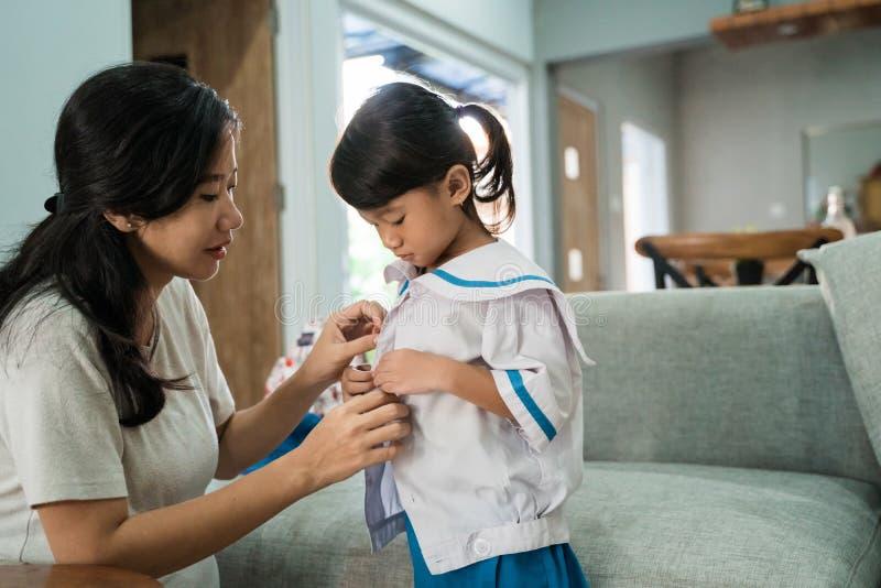 Tragende Schuluniform des Kindergartenstudenten morgens zu Hause lizenzfreie stockbilder