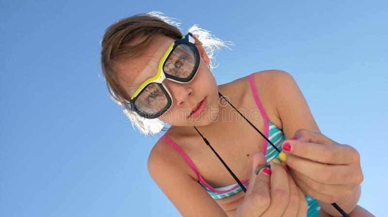 Tragende Schutzbrillen des Mädchens mit Kieseln stockbild