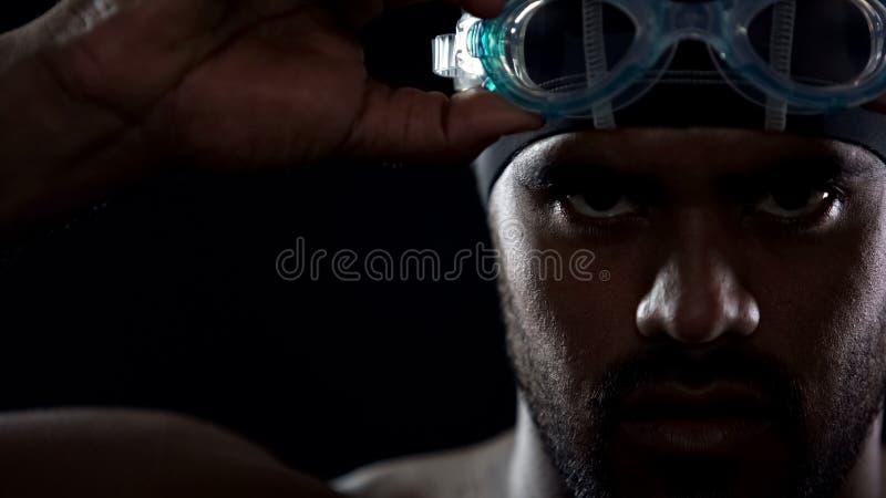 Tragende Schutzbrillen des männlichen hispanischen Schwimmers, Athlet, der ernsthaft Kamera betrachtet lizenzfreie stockbilder