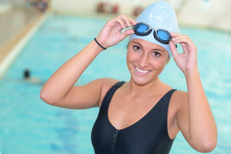 Tragende Schutzbrillen und Hut des weiblichen Schwimmers des Porträts lizenzfreies stockbild