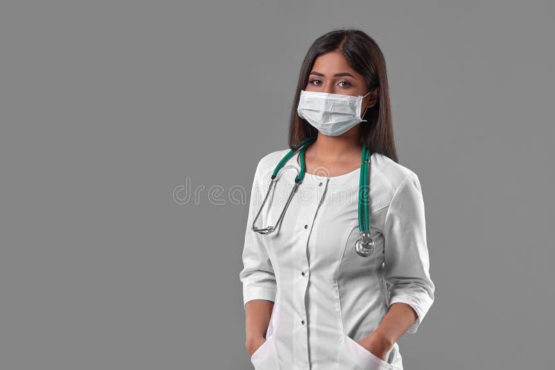 Tragende Schutzmaske der jungen Ärztin mit Stethoskop stockfotos
