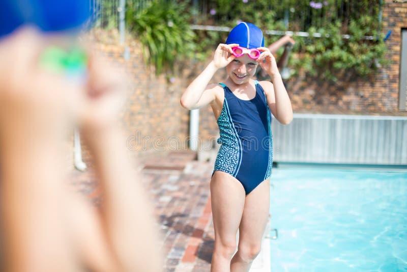 Tragende Schwimmenschutzbrille des kleinen Mädchens am Poolside lizenzfreie stockfotos
