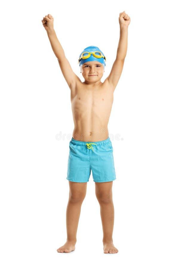 Tragende Schwimmenstämme des Jungen, die seine Hände hochhalten stockfotografie