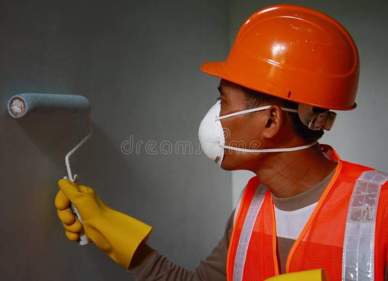 Tragende Sicherungsarbeiten der Malerarbeitskraft auf Job lizenzfreie stockfotografie