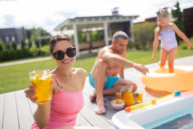 Tragende Sonnenbrille der Frau, die Cocktail beim Ein Sonnenbad nehmen nahe Pool trinkt stockfotos