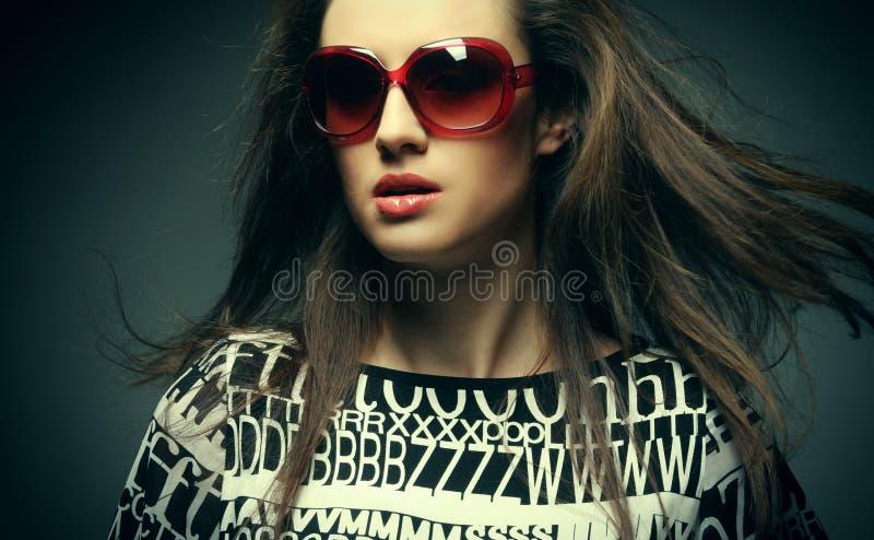 Tragende Sonnenbrille der schönen Modefrau über grauem Hintergrund stockfotografie