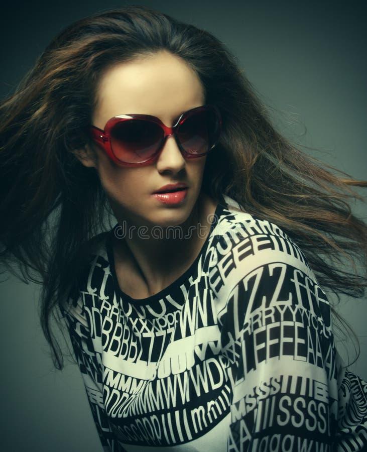 Tragende Sonnenbrille der schönen Modefrau über grauem Hintergrund lizenzfreies stockfoto