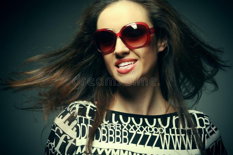 Tragende Sonnenbrille der schönen Modefrau über grauem Hintergrund stockfoto