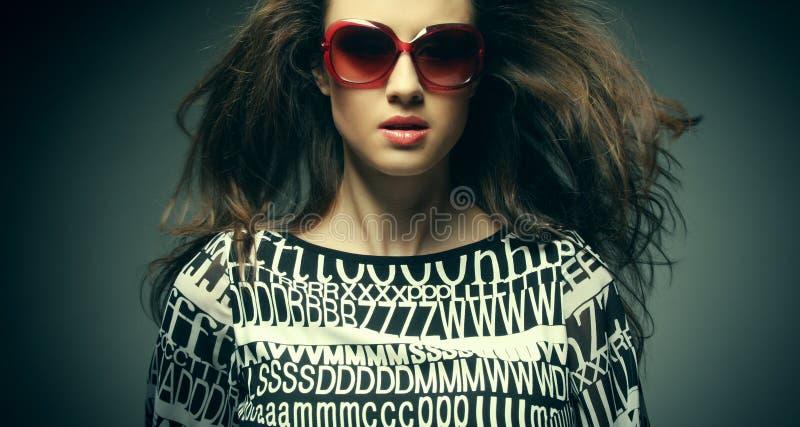 Tragende Sonnenbrille der schönen Modefrau über grauem Hintergrund lizenzfreie stockfotos