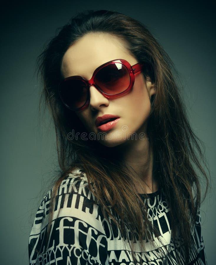 Tragende Sonnenbrille der schönen Modefrau über grauem Hintergrund stockbild