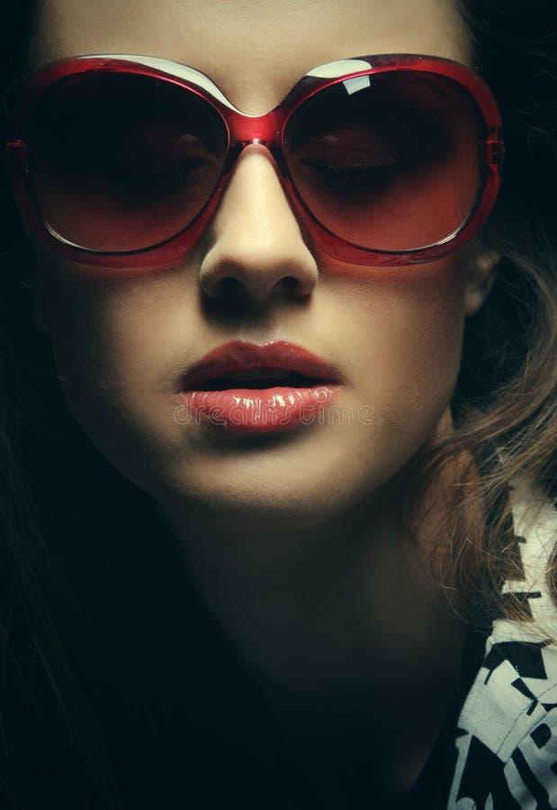 Tragende Sonnenbrille der schönen Modefrau über grauem Hintergrund lizenzfreies stockbild
