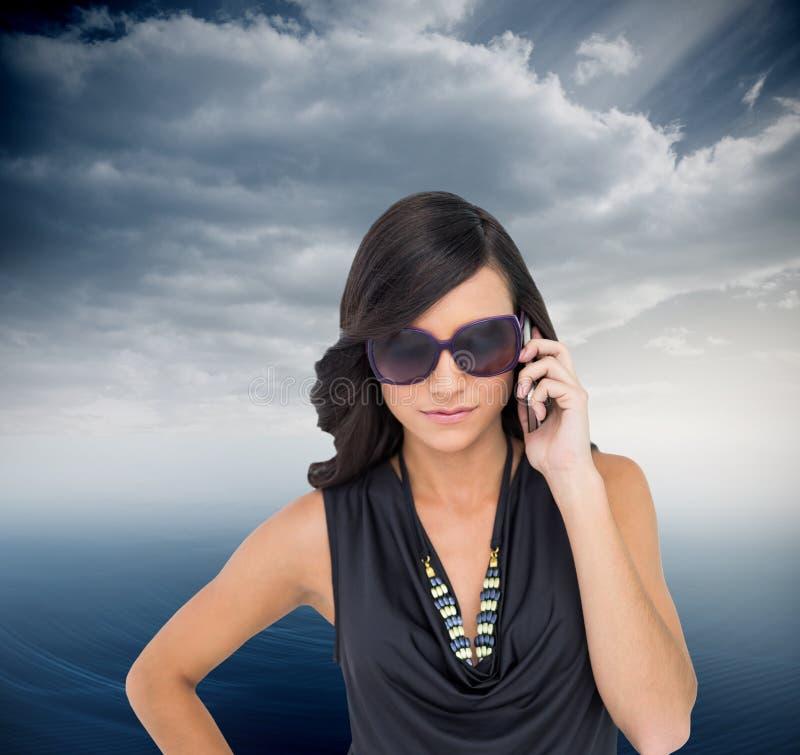 Tragende Sonnenbrille des ernsten eleganten Brunette am Telefon stock abbildung