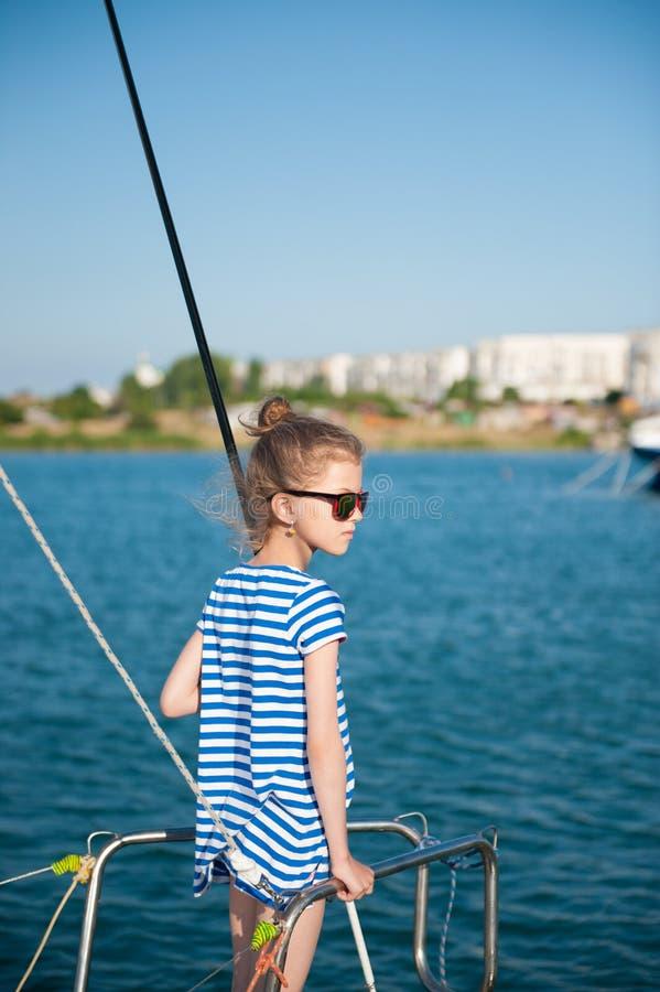 Tragende Sonnenbrille des hübschen kleinen Mädchens und gestreiftes Hemd an Bord des Schiffes im Seehafen lizenzfreies stockbild
