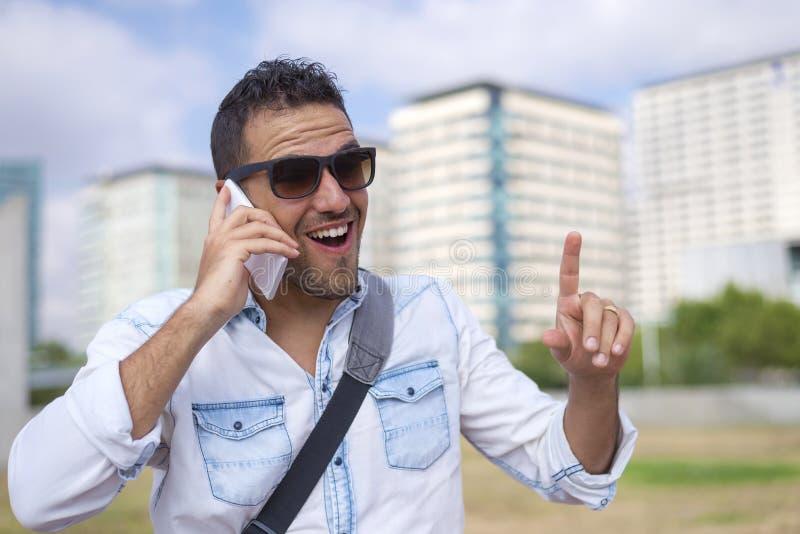 Tragende Sonnenbrille des jungen Mannes bei der Anwendung des Handys in der Straße stockfoto