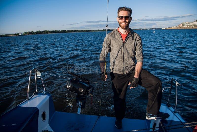 Tragende Sonnenbrille des jungen Mannes, die auf Yachtheck steht und perfekten Herbsttag unter Segeln - Segeln von Feiertagen gen lizenzfreie stockfotografie