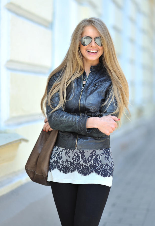 Tragende Sonnenbrille des Mode-Modells mit der Tasche, die draußen lächelt lizenzfreies stockbild