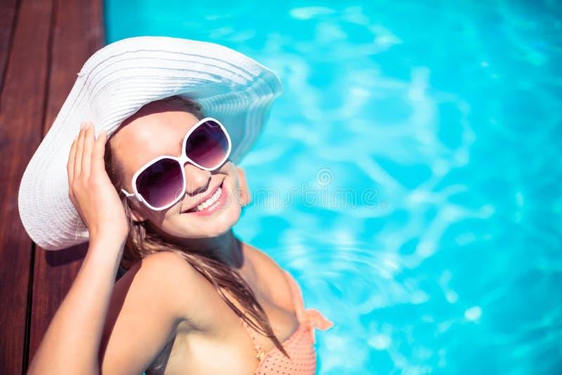 Tragende Sonnenbrille und Strohhut der Schönheit, die auf hölzerner Plattform durch Poolside sich lehnen stockbild