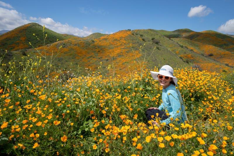 Tragende Sonnenbrille- und Strohhuthaltungen der jungen Frau auf dem Mohnblumengebiet in Kalifornien lizenzfreie stockfotografie