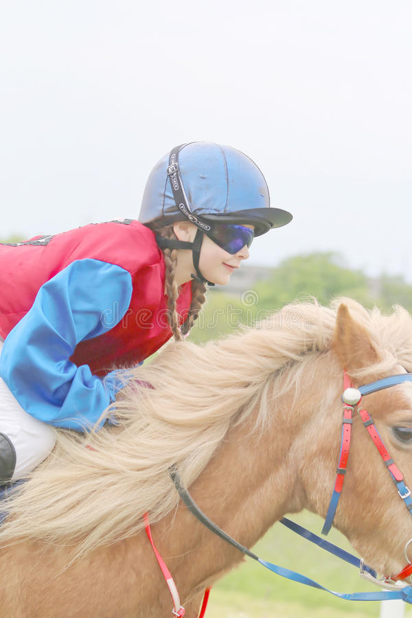Tragende Sonnenbrillen des jungen Mädchens, die ein Pony reiten stockbilder