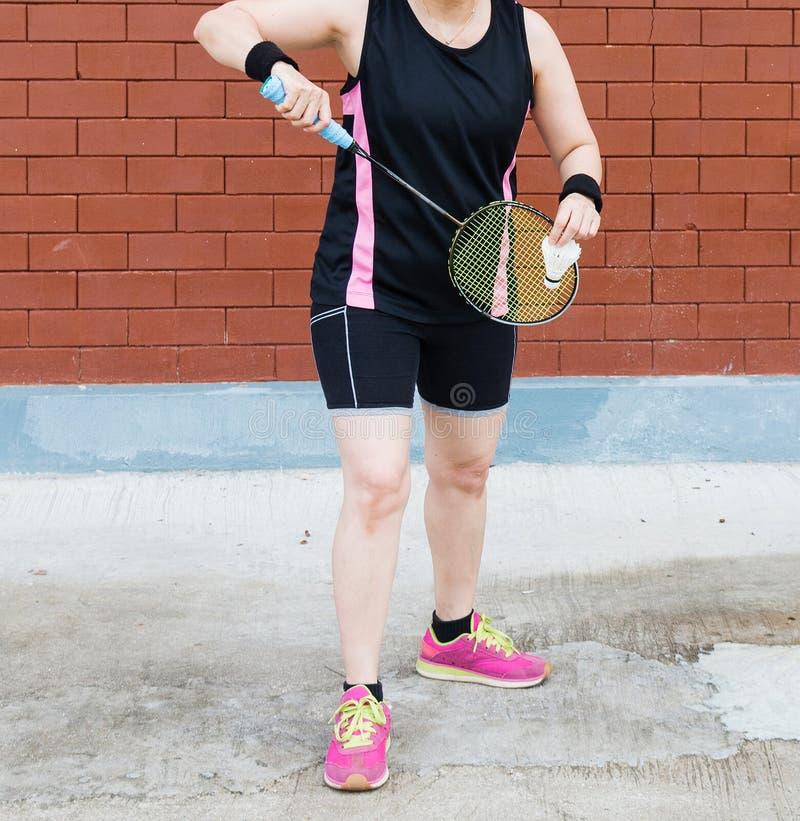 tragende Sportkleidung des Badmintonfrauen-Spielers, die racke halten steht lizenzfreies stockbild