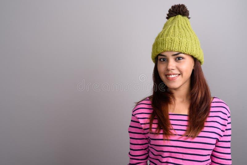 Tragende Strickmütze der jungen schönen indischen Frau gegen graues Ba stockbild