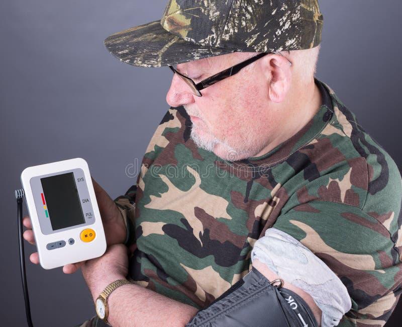 Tragende Tarnungskleidung des älteren älteren Mannes, die seinen Blutdruck überprüft lizenzfreie stockfotografie