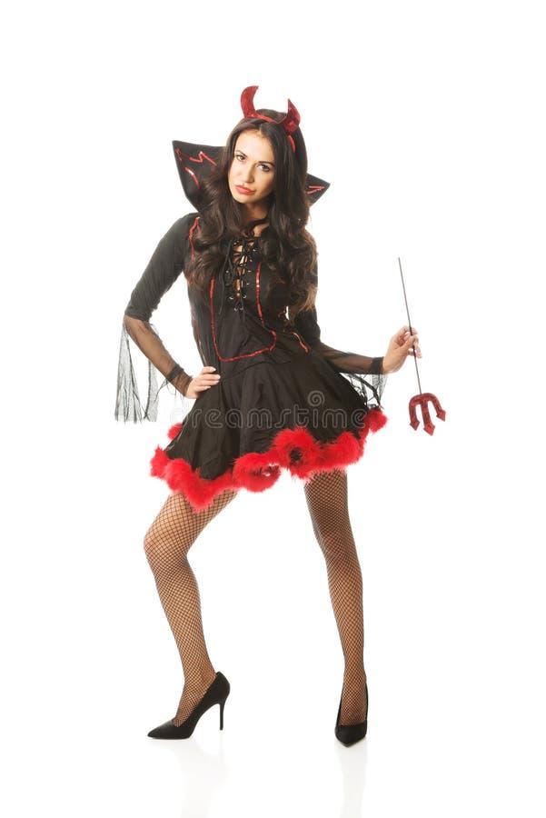tragende Teufelkleidung der Frau, Double mit gespreizten Beinen, Dreizack halten stockfoto