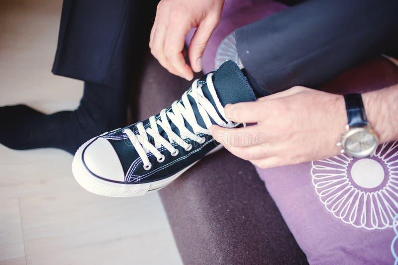 tragende Turnschuhe des Bräutigams oder des Geschäftsmannes anstelle der klassischen Schuhe stockbilder