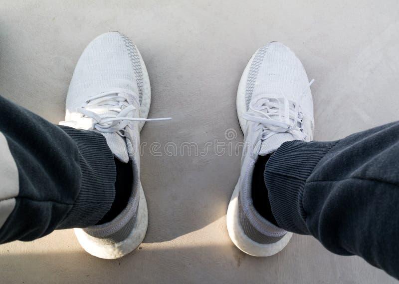 Tragende Turnschuhe eines Mannes, ADIDAS ULTRA LADEN auf, weiße und graue Schuhe lizenzfreie stockbilder