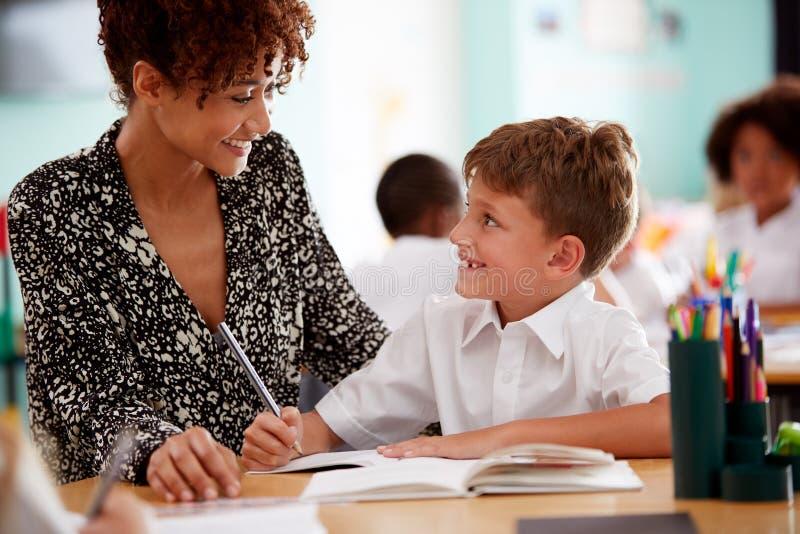 Tragende Unterstützung Frauen-grundlegender Schullehrer-Giving Male Pupils Uniform-eine bis eine im Klassenzimmer lizenzfreies stockfoto