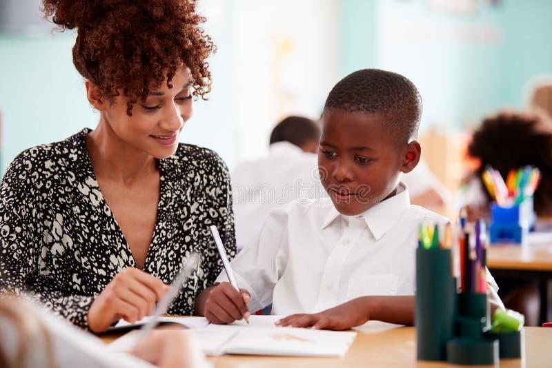 Tragende Unterstützung Frauen-grundlegender Schullehrer-Giving Male Pupils Uniform-eine bis eine im Klassenzimmer lizenzfreie stockfotografie