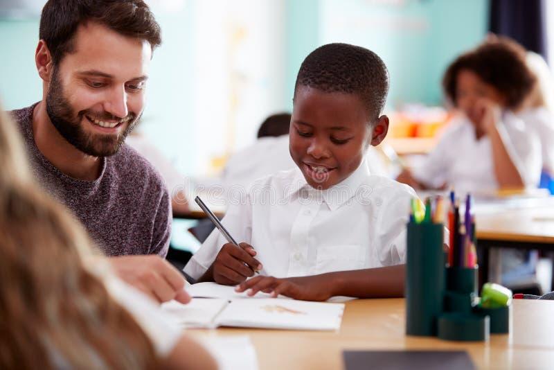 Tragende Unterstützung grundlegender Schullehrer-Giving Male Pupils Uniform-eine bis eine im Klassenzimmer lizenzfreies stockfoto