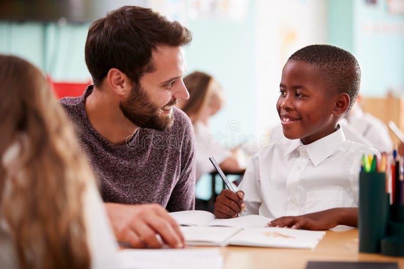 Tragende Unterstützung grundlegender Schullehrer-Giving Male Pupils Uniform-eine bis eine im Klassenzimmer lizenzfreie stockfotografie
