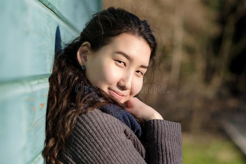 Tragende warme Jacke der jungen asiatischen Frau im Freien, die nahe hölzerner blauer Wand am sonnigen Herbsttag steht lizenzfreie stockfotografie