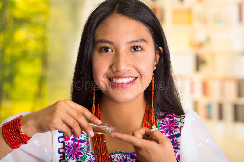 Tragende weiße Bluse der schönen hispanischen Frau mit der bunten Stickerei, kosmetisches Produkt auf Finger während zutreffend stockfoto
