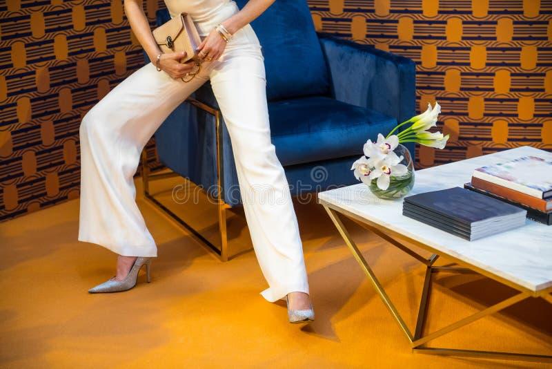 Tragende weiße Hosen des Haute Couture-Modells und silberne hohe Absätze, die eine Tasche mit Schmuck halten stockfotografie
