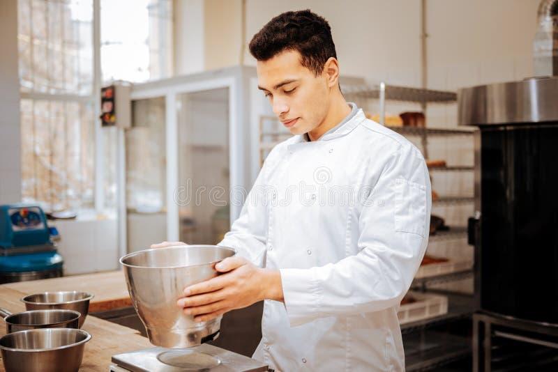 Tragende weiße Jackenstellung des erfahrenen Bäckers nahe Küchenskala lizenzfreies stockbild