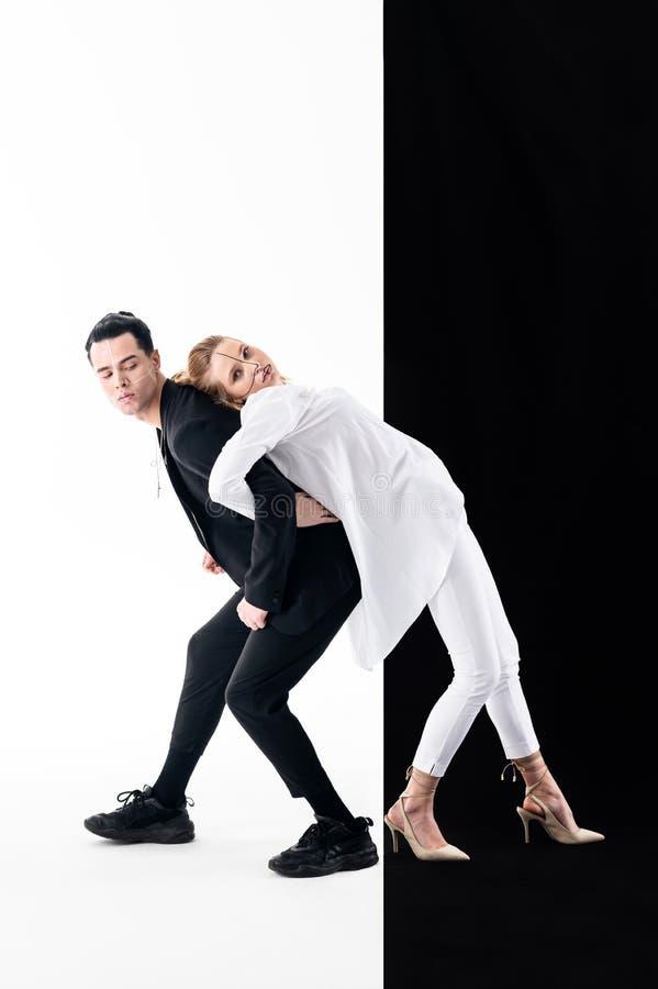 Tragende weiße Kleidung des blonden Modells, die auf Rückseite ihres Kollegen sich lehnt stockbilder
