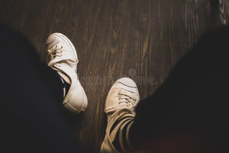 Tragende weiße Turnschuhe des Mannes in der schwarzen Hose, die auf Kaffeestube sitzt lizenzfreie stockfotos