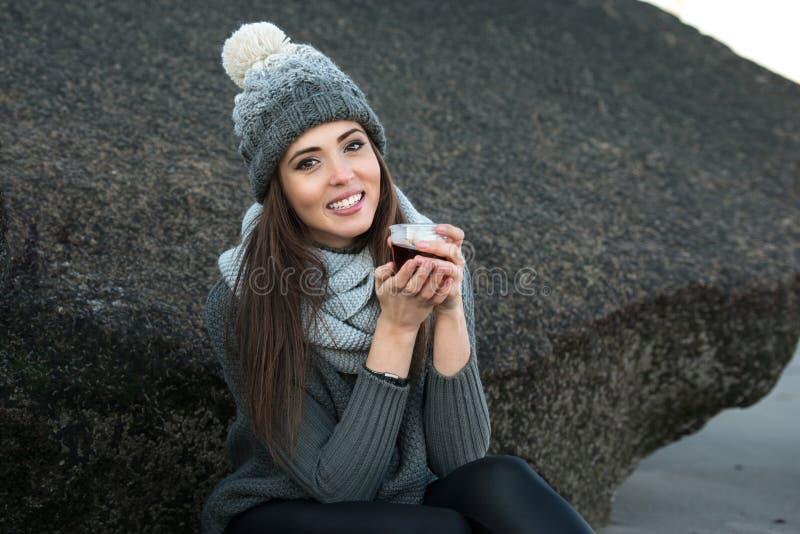Tragende Winterkleidung der Frau, die draußen Kaffee trinkt stockfoto